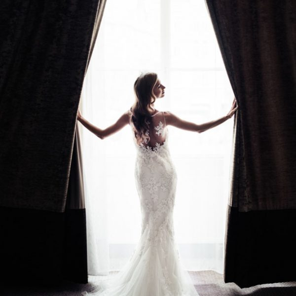 a young beautiful bride in a morning lit window